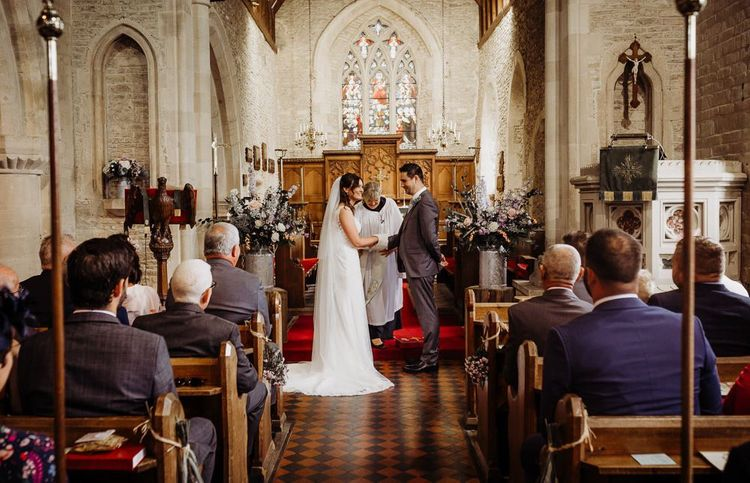 Bride and groom say their vows at intimate church ceremony with pastel floral decor