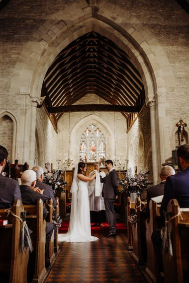 Bride and groom say their vows at church ceremony with laced bridal dress and long veil