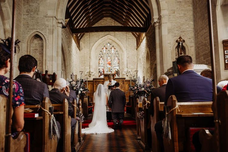 Bride and groom tie the knot at church ceremony with floral decor