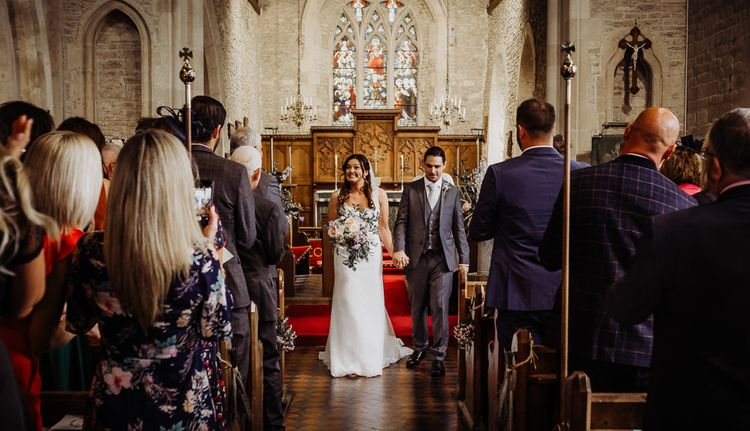 Bride wearing laced dress and pastel floral bouquet with groom wearing grey three piece suit and tie