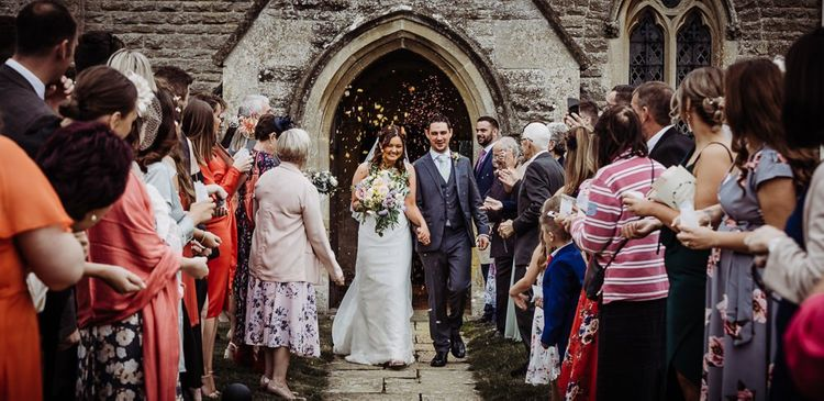 Confetti shot as bride and groom leave the church ceremony holding a beautiful pastel floral bouquet