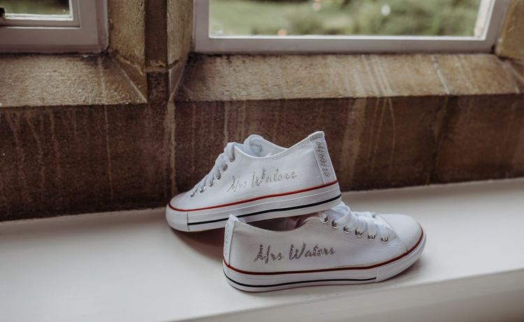 Personalised bridal trainers with embellished writing at rustic barn wedding in The Cotswolds