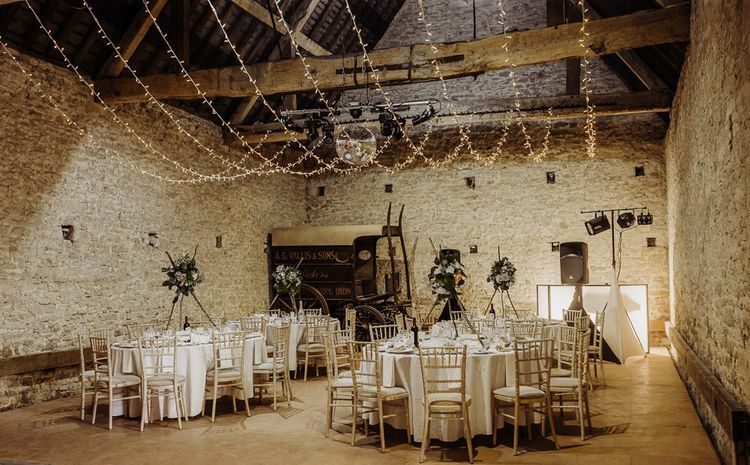 Cogges Manor Farm wedding reception with hanging fairy lights and floral centrepieces