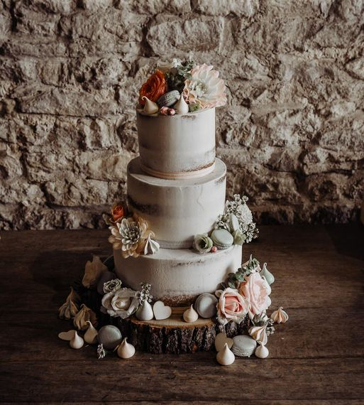 Semi naked wedding cake decorated with florals and macaroons
