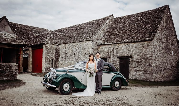 Bride and groom arrive in vintage wedding car to Cogges Manor Farm
