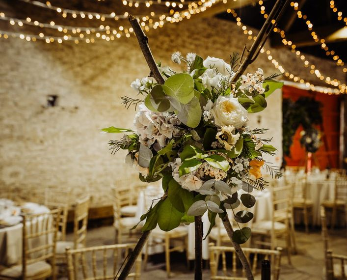Beautiful floral centrepieces at rustic reception with hanging fairy lights