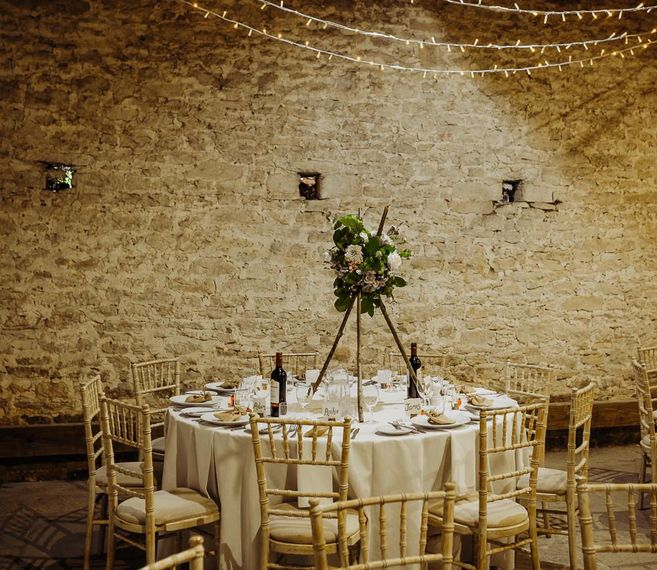 Cogges Manor Farm wedding reception with floral table arrangements and hanging fairy lights