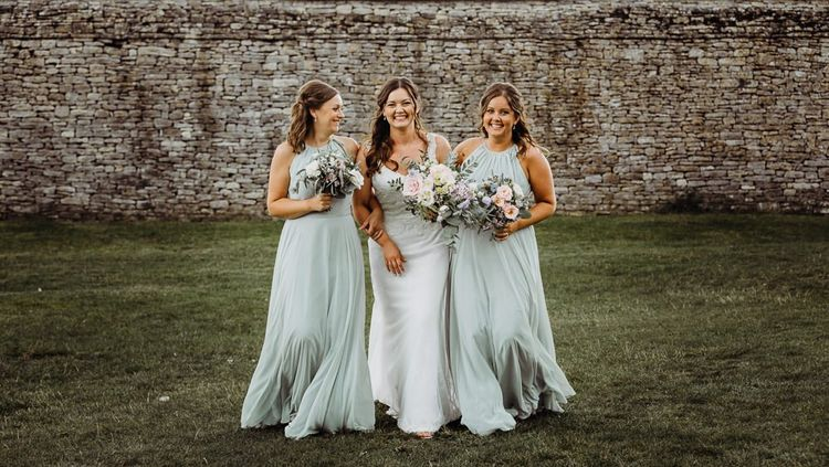 Bride wearing beautifully laced dress with her bridesmaids holding pastel floral bouquets