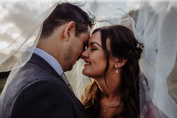 Bride and groom embrace featuring the brides beautiful veil and delicate earrings