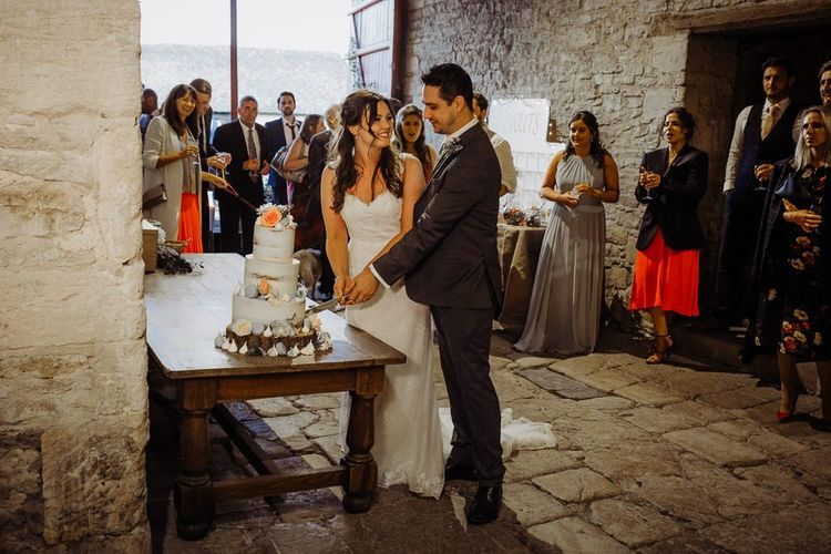 Bride and groom cut their cake at rustic wedding with floral decor
