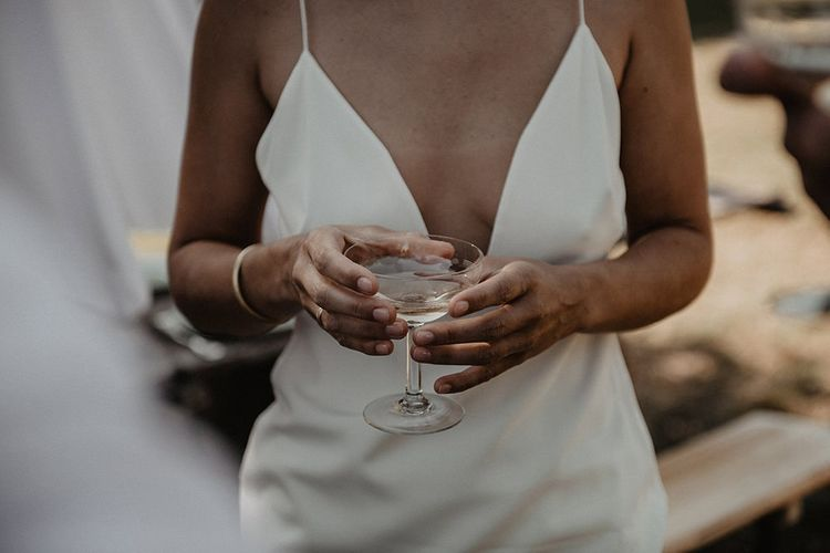 Bride sips champagne as she prepares for intimate wedding