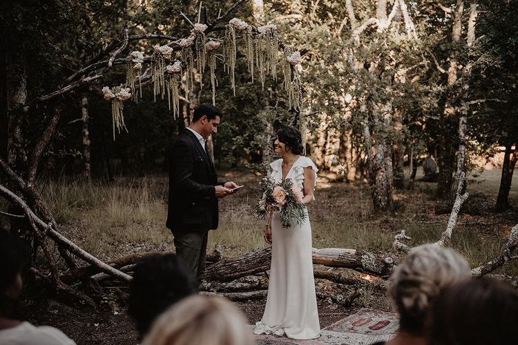 Bride and groom exchange vows in outdoor small  wedding ceremony