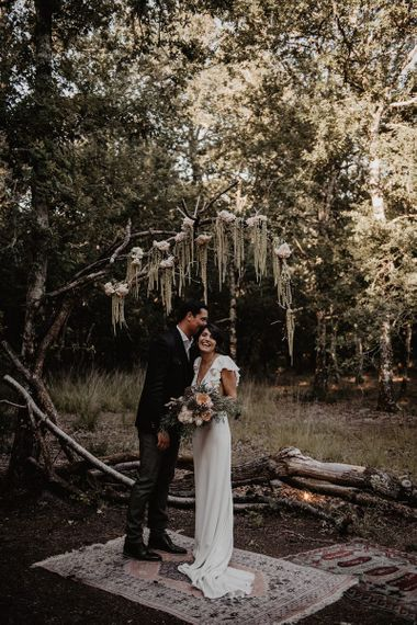 Bride and groom exchange vows in outdoor intimate wedding ceremony with stunning flower decor
