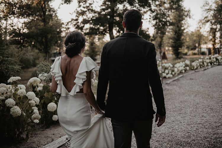Ruffle sleeve wedding dress with groom in black suit