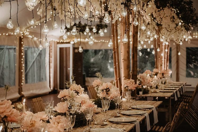 Blush wedding table decor with candles and hanging light installation
