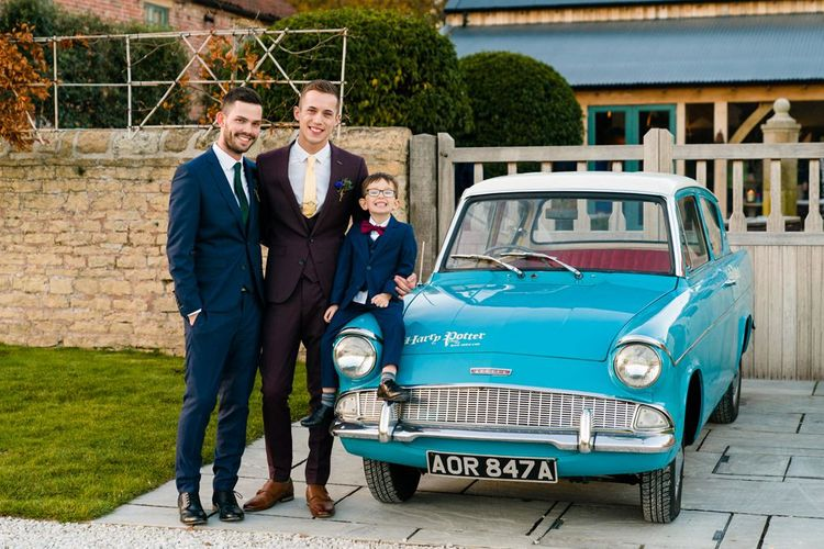 Grooms in Burgundy and Navy Remus Uomo Suits Standing Next to Ford Anglia Wedding Car
