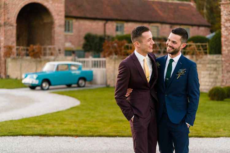 Grooms in Burgundy and Navy Remus Uomo Suits Embracing Outside Hazel Gap Barn