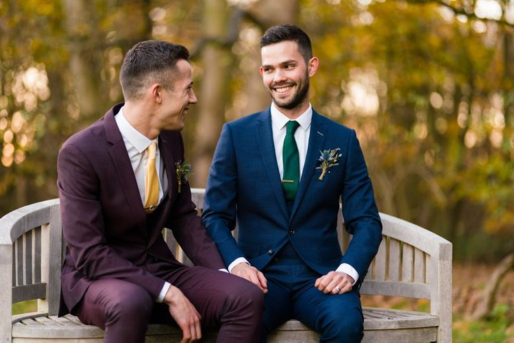 Two Grooms in Burgundy and Navy Remus Uomo Suits Sitting on a Bench