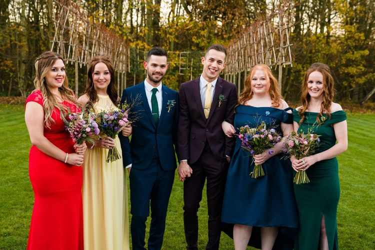 Two Grooms in Burgundy and Navy Remus Uomo Suits and Bridesmaids in Bright Dresses