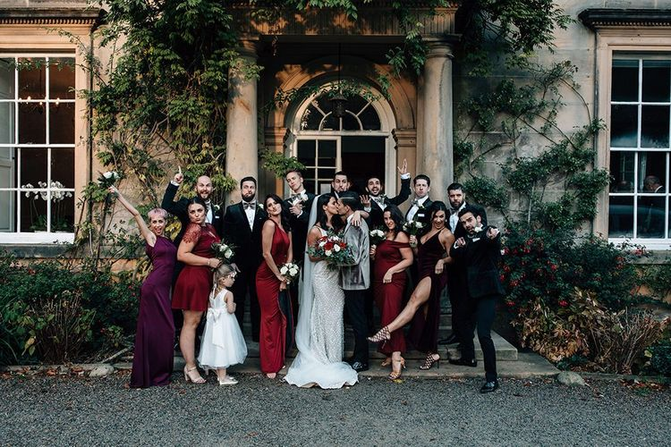 Wedding Party Portrait with Groomsmen in Tuxedos and Bow Ties and Bridesmaids in Burgundy Dresses