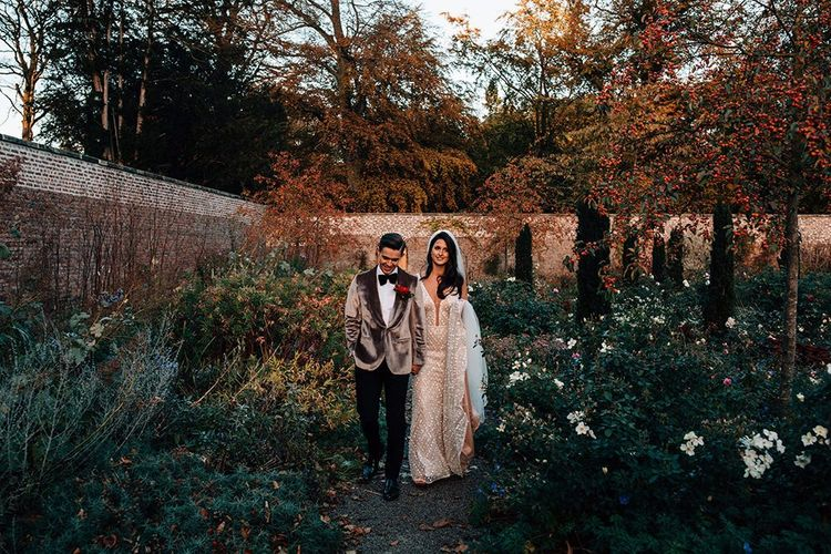 Groom in Grey Velvet Dinner Jacket and Bride in Sequin Wedding Dress Walking in Middleton Lodge's Gardens