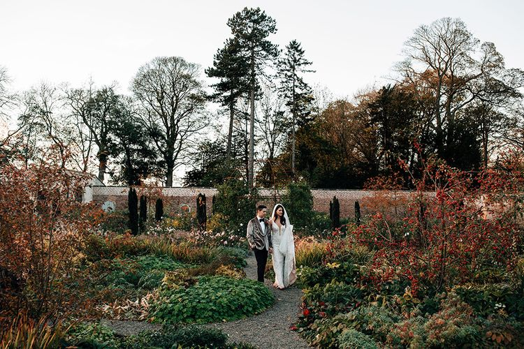 Bride in Sequin Wedding Dress and Groom in Grey Velvet Dinner Jacket Walking in Middleton Lodge's Gardens