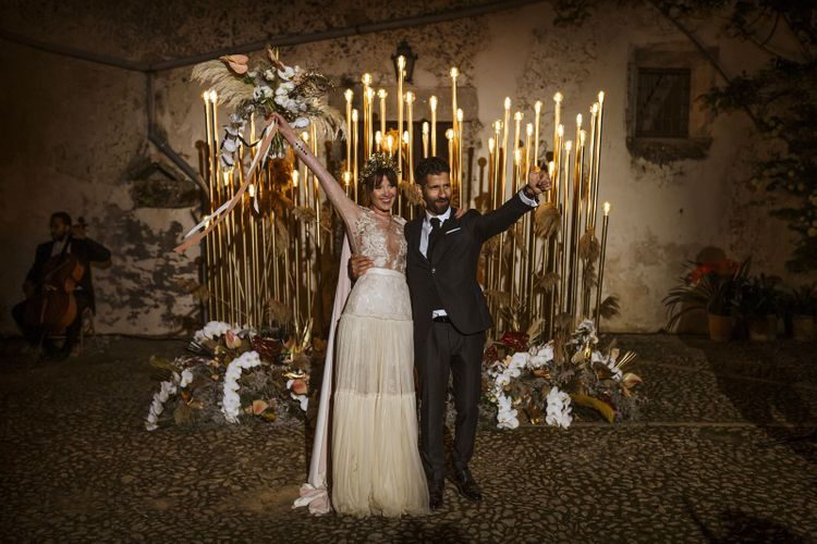 Bride and Groom Standing in Front of Gold Wedding Lighting  just Married
