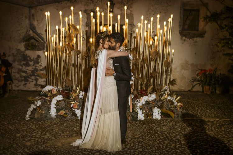 Bride and Groom Embracing in Front of Gold Wedding Lighting  Backdrop