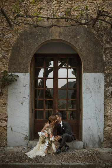 Bride and Groom Kissing on Steps of Mallorca Venue