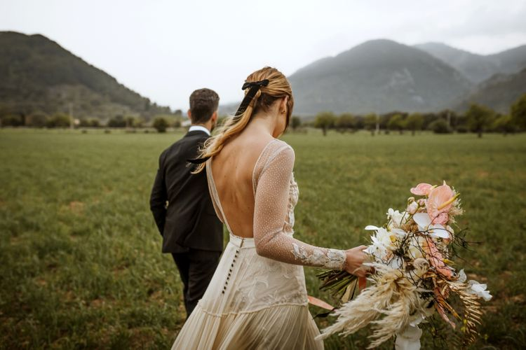 Bride in Backless Wedding Dress with Long Sleeves
