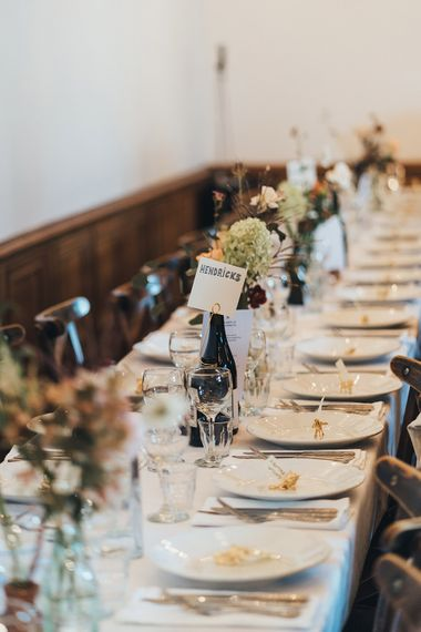 Banquet Tables | Wooden Chairs | Hendricks Gin Table Sign | Bud Vases | Gold Giraffe Place Settings | Wedding Reception at Clapton Country Club | Metallic Confetti Cannons and Paper Lanterns with Bride in Beaded Shoulder Eliza Jane Howell Dress | Miss Gen Photography