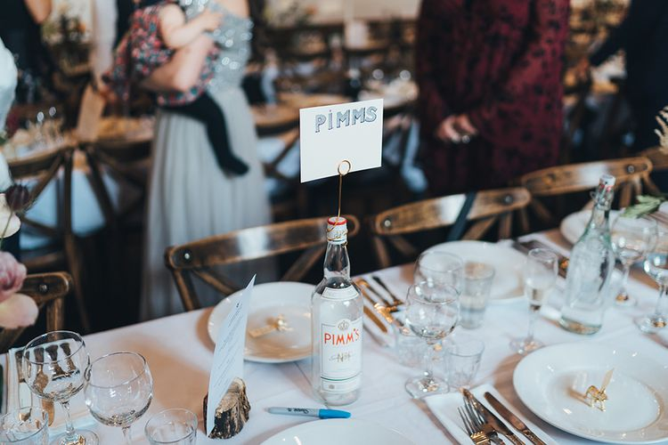 Banquet Tables | Wooden Chairs | Pimms Bottle Table Sign | Log Slice Displaying Wedding Breakfast Menu | Gold Giraffe Place Settings | Wedding Reception at Clapton Country Club | Metallic Confetti Cannons and Paper Lanterns with Bride in Beaded Shoulder Eliza Jane Howell Dress | Miss Gen Photography