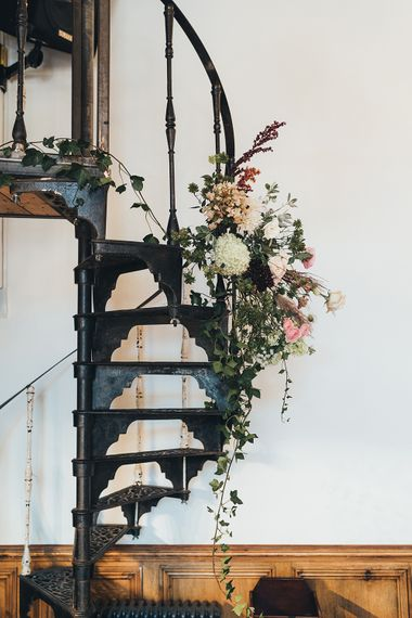 Floral Display Hanging from Winding Metallic Staircase | Wedding Reception at Clapton Country Club | Metallic Confetti Cannons and Paper Lanterns with Bride in Beaded Shoulder Eliza Jane Howell Dress | Miss Gen Photography