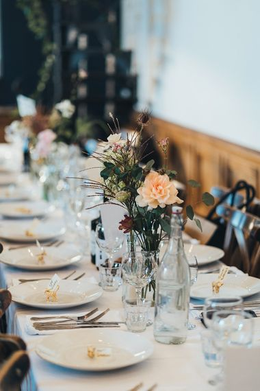 Bud Vase with Peach Flowers and Foliage | Gold Giraffe Place Settings | Wedding Reception at Clapton Country Club | Metallic Confetti Cannons and Paper Lanterns with Bride in Beaded Shoulder Eliza Jane Howell Dress | Miss Gen Photography