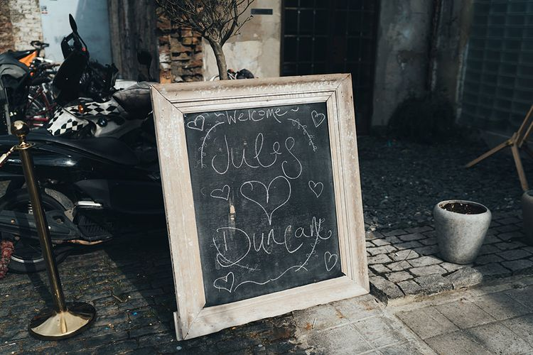 Chalkboard Welcome Sign | Wedding Reception at Clapton Country Club | Metallic Confetti Cannons and Paper Lanterns with Bride in Beaded Shoulder Eliza Jane Howell Dress | Miss Gen Photography