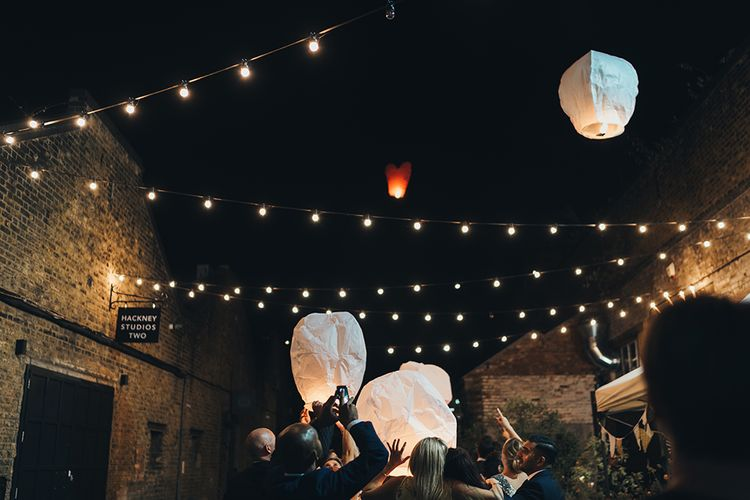 Wedding Guests Letting Off Paper Lanterns | Festoon Lights | Clapton Country Club Wedding Reception | Metallic Confetti Cannons and Paper Lanterns with Bride in Beaded Shoulder Eliza Jane Howell Dress | Miss Gen Photography