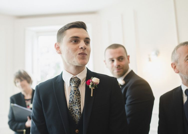 Groom in blue wedding suit and patterned tie