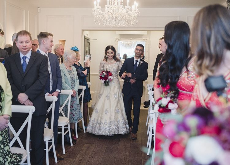 Bride walks down the altar at multicultural wedding with red bridesmaid dresses