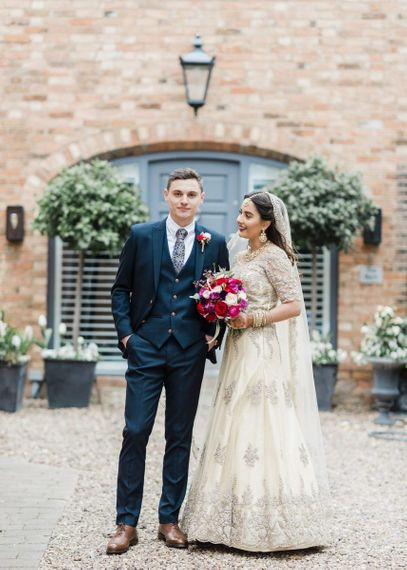 Bride and groom at multicultural wedding with red bridesmaid dresses