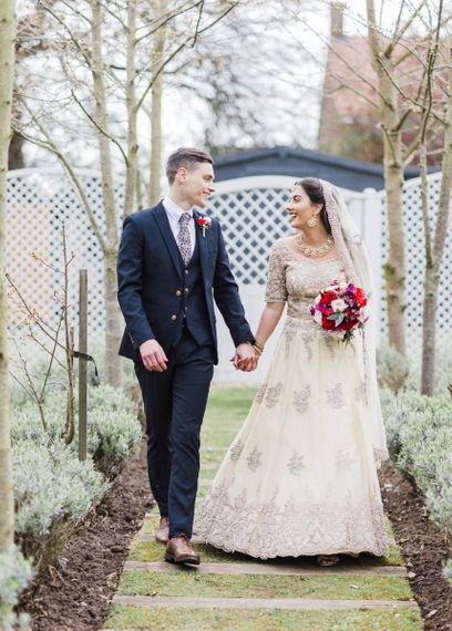 Bride and groom at fusion wedding with red bridesmaid dresses