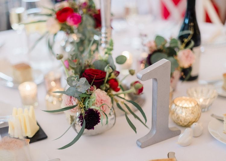 Bright wedding flowers at fusion wedding with red bridesmaid dresses