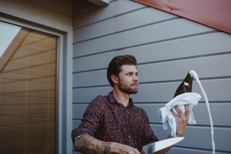 Cutting The Champagne Bottle //  Groom In Burgundy Suit // Exclusive Hire Wedding Venue In Nida Lithuania // Images By Motiejus