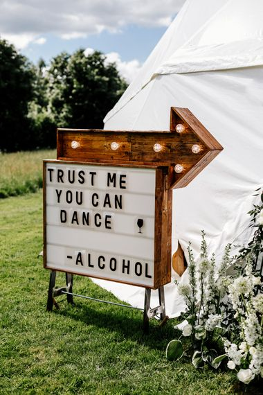 Wooden Wedding Sign // Bride In Floral Dress By Stephanie Allin Festival Wedding With Food Trucks & Outdoor Ceremony With Geo Dome Tent Baya Hire Epic Love Story Photography
