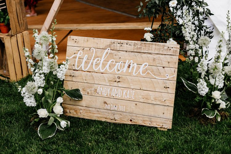 Wooden Welcome Sign For Wedding // Bride In Floral Dress By Stephanie Allin Festival Wedding With Food Trucks & Outdoor Ceremony With Geo Dome Tent Baya Hire Epic Love Story Photography