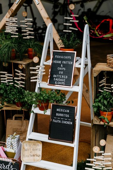 Rustic Table Plan For Wedding With Ladders // Bride In Floral Dress By Stephanie Allin Festival Wedding With Food Trucks & Outdoor Ceremony With Geo Dome Tent Baya Hire Epic Love Story Photography
