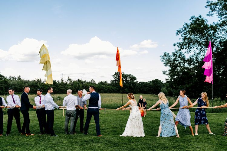 Tug Of War Wedding Games // Bride In Floral Dress By Stephanie Allin Festival Wedding With Food Trucks & Outdoor Ceremony With Geo Dome Tent Baya Hire Epic Love Story Photography