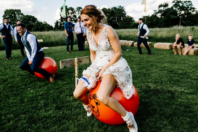Space Hopper Race Wedding Games // Bride In Floral Dress By Stephanie Allin Festival Wedding With Food Trucks & Outdoor Ceremony With Geo Dome Tent Baya Hire Epic Love Story Photography