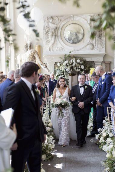 走在与白色玫瑰花束的走道的新娘