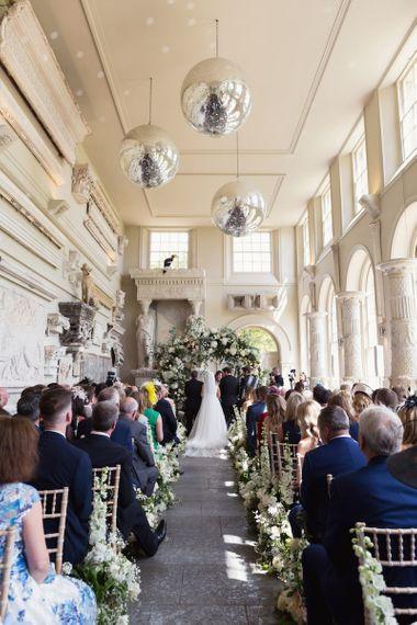 新娘和新郎在与白色花卉装饰的Aynhoe公园系结