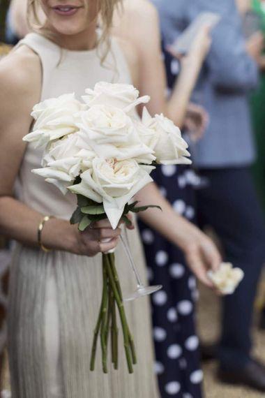 伴娘美丽的边缘礼服和白色玫瑰花束